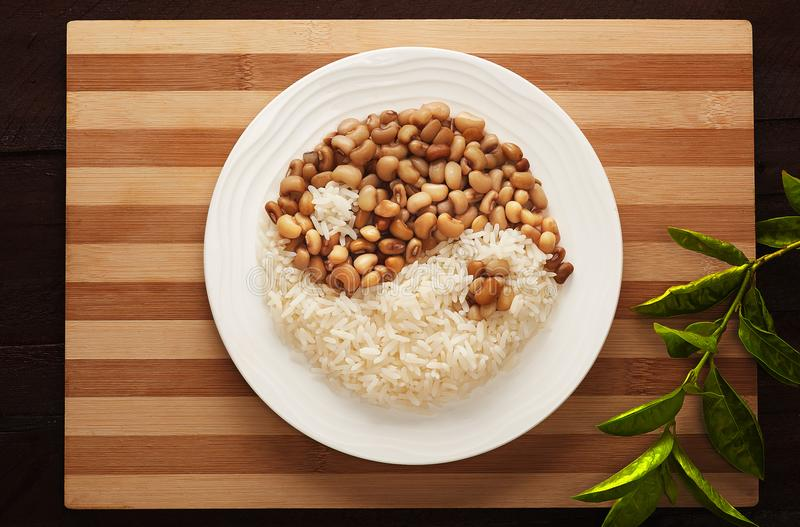 Rice and beans yin yang. Rice and Beans, Nigerian`s most popular meal in a yin yang creative form royalty free stock image
