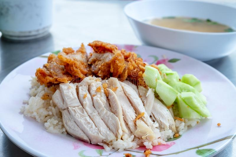 Rice with boiled chicken and the fried chicken place on top served with cucumbers stock photo