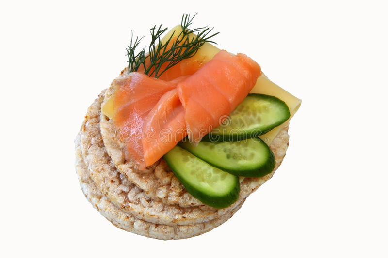 Rice cakes with salmon. Thin rice cakes with smoked salmon and cheese and vegetables isolated on white background royalty free stock images