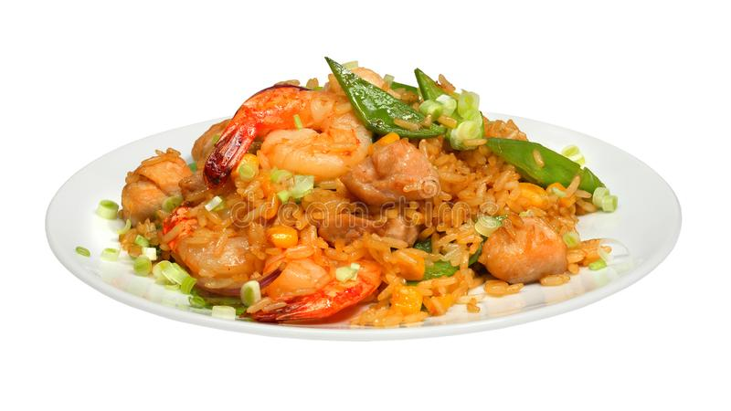 Rice with chicken meat, shrimps and vegetables on white round plate stock image