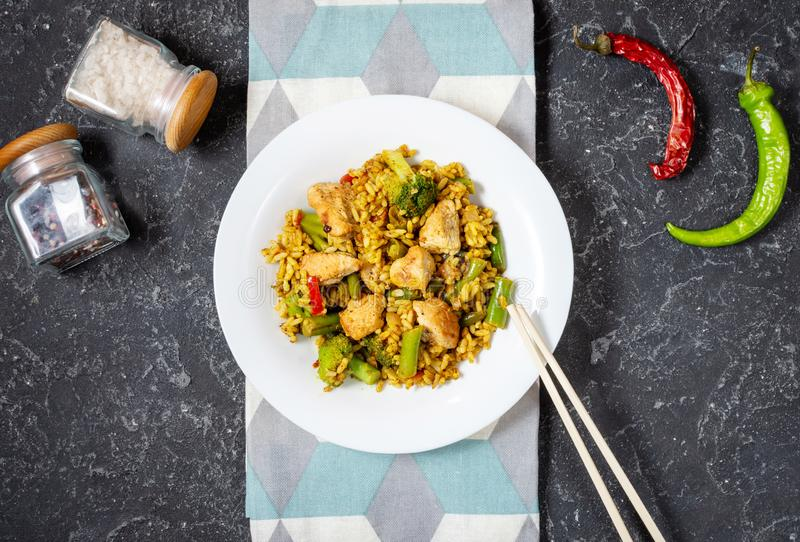 Rice with chicken meat and vegetables in a plate on black stone table stock images