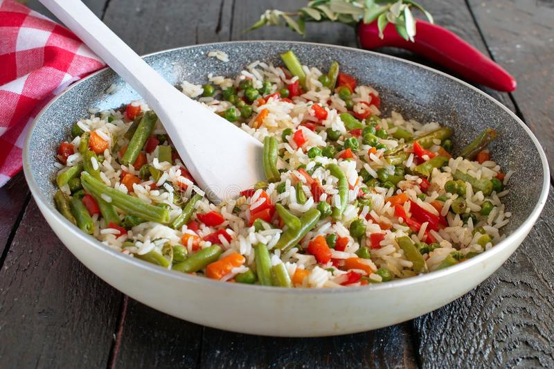 Rice cooked with vegetables and olive oil in a frying pan. Healthy eating concept. Fasting food stock image