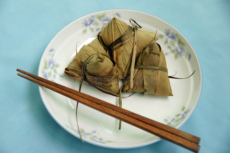 Rice dumpling. Steamed Chinese rice dumplings (zongzi) wrapped in bamboo leaves, filled with glutinous/sticky rice, pork, mushrooms, and peanuts. These are eaten royalty free stock photo