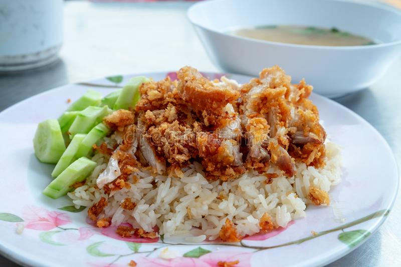 Rice with the fried chicken place on top served with cucumbers royalty free stock photos