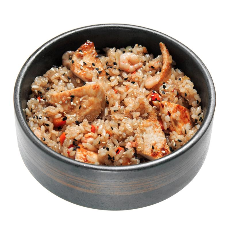 Rice with fried chicken, shrimps, vegetables and sesame in the black bowl. Isolated on white background royalty free stock image