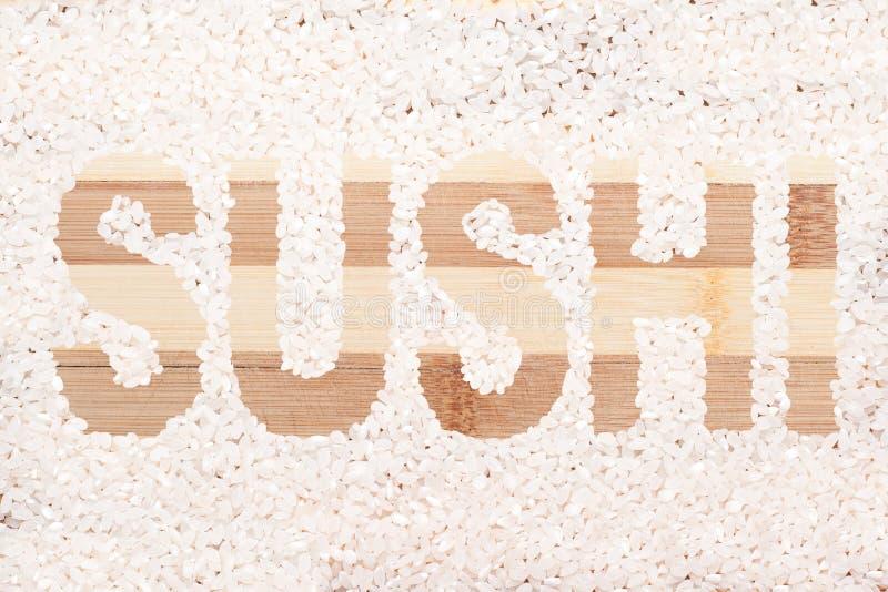 Rice grain. Word sushi written on wooden cutting board royalty free stock photo