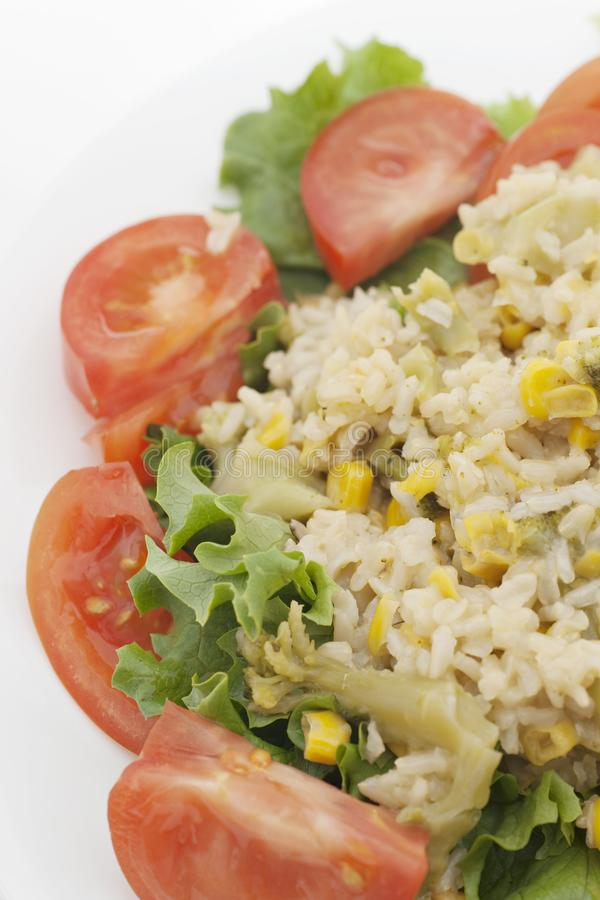 Rice hotdish with lettuce and tomatoes. Vertical photography of rice hotdish with lettuce and tomatoes isolated on white stock image
