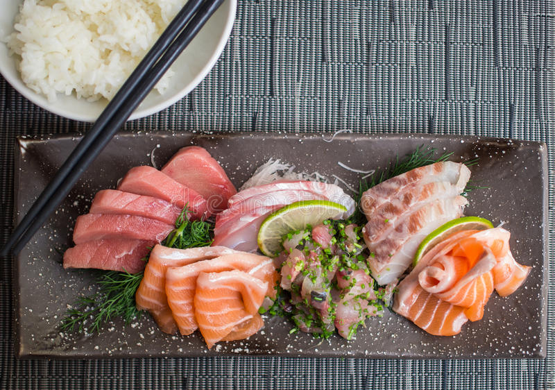 Rice and Japanese sashimi on a black dish. Japanese raw fish. Also known as Sashimi stock images