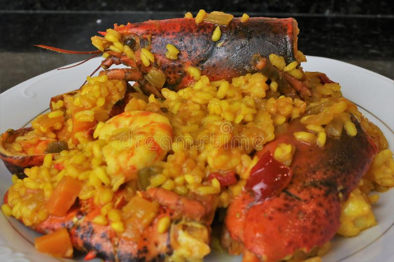 Rice with lobster seafood paella. The rice paella with lobster is a typical dish of Andalusian and Spanish cuisine. In focus the head of the lobster as the main stock photos