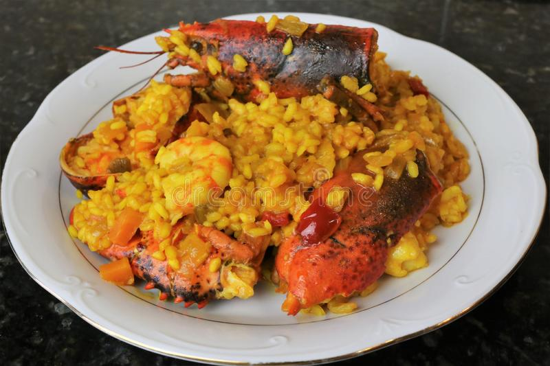 Rice with lobster seafood paella. The rice paella with lobster is a typical dish of Andalusian and Spanish cuisine. In focus the head of the lobster as the main royalty free stock images