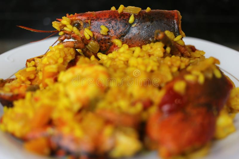 Rice with lobster seafood paella. The rice paella with lobster is a typical dish of Andalusian and Spanish cuisine. In focus the head of the lobster as the main royalty free stock photo