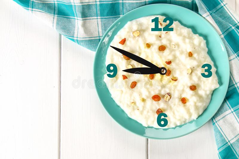 Rice milk porridge with nuts and raisins in a blue dish on a white wooden table. The concept of a breakfast with a clock. royalty free stock image