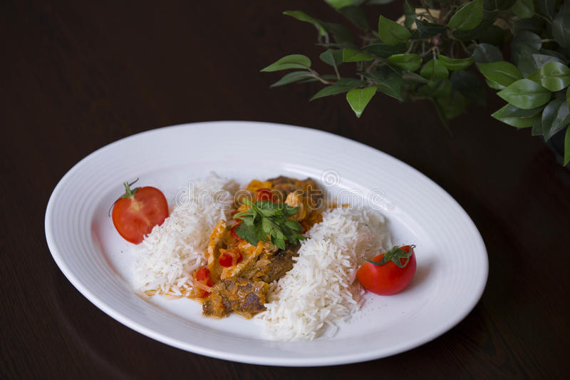 Rice with minced meat and tomato sauce. Chicken curry with rice and cilantro on white plate close up horizontal. stock photo