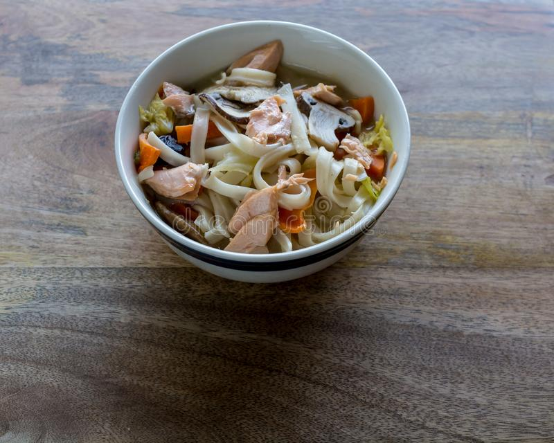 Rice Noodle soup with vegetables and salmon, closeup and top vie. W, on wooden table background, ready to eat royalty free stock images