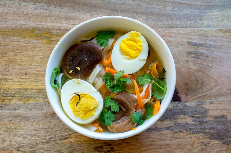 Rice Noodle soup with vegetables and salmon, closeup and top vie. Rice Noodle soup with vegetables and split egg in half, closeup and top view, on wooden table stock images