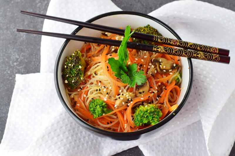 Rice noodles with carrot, broccoli and mushrooms in a black bowl on a black abstract background. Asian food. Healthy stock photo