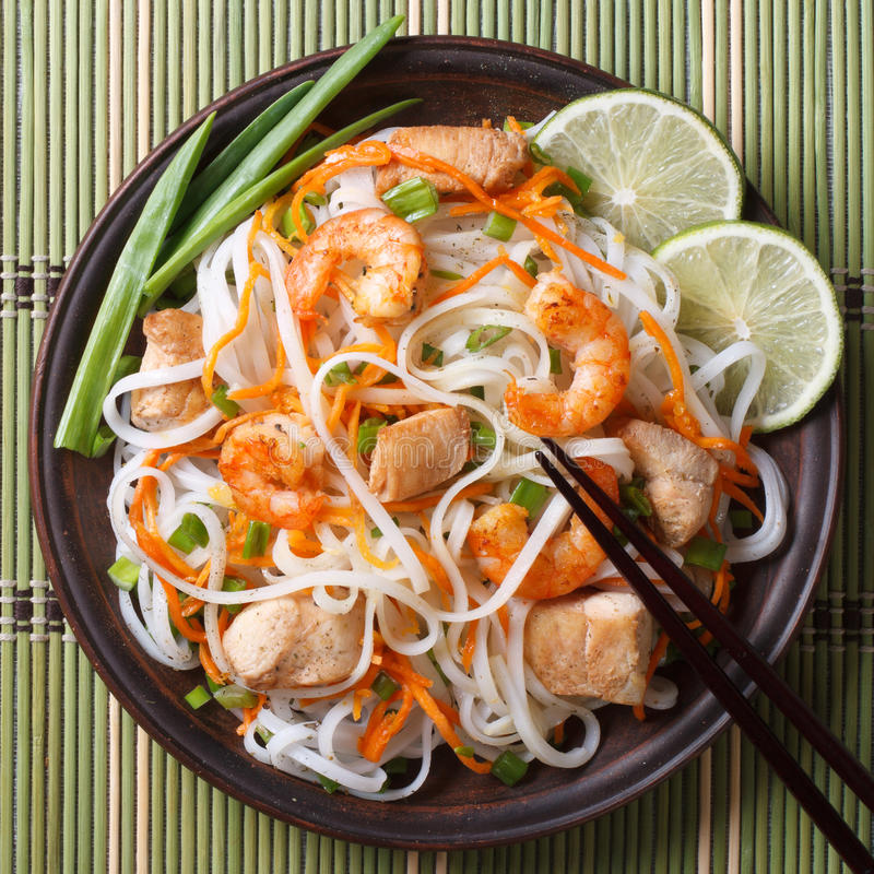 Rice noodles with chicken, shrimp and vegetables closeup stock photography