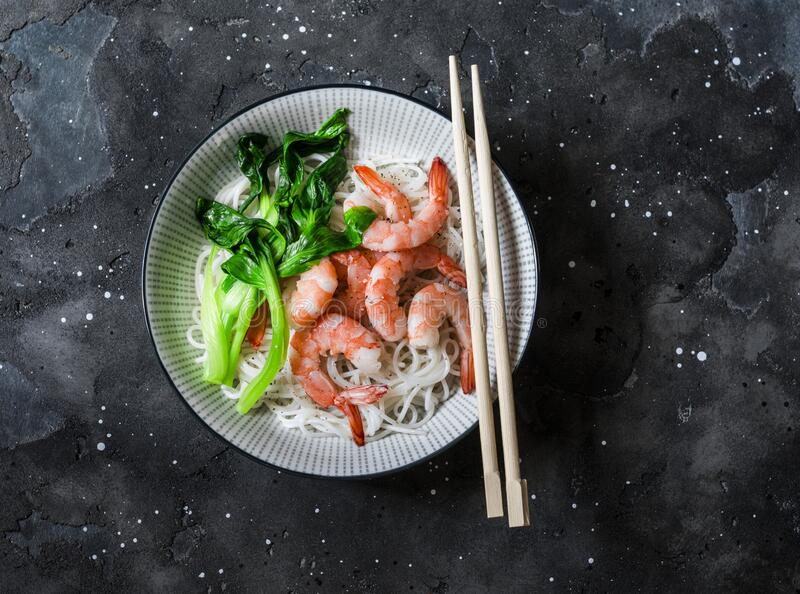 Rice noodles with poached shrimp and bok choy cabbage on a dark background, top view.  stock photos