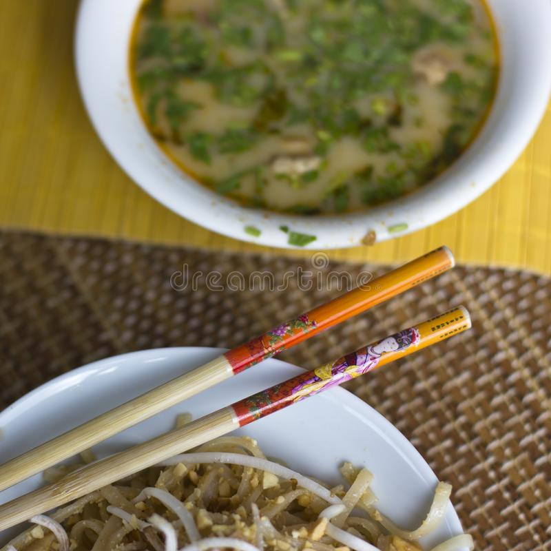 Rice noodles with sprouted soy and spicy soup Tom Yam with shrimps and greens royalty free stock image