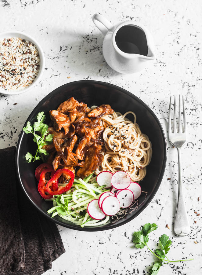 Rice noodles and teriyaki chicken stir fry with quick pickled cucumbers and radishes. On a light background, top view. Asian food style royalty free stock photography