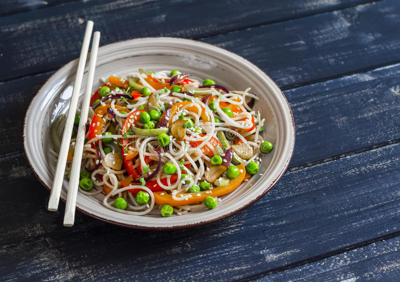 Rice noodles with vegetable stir fry on the ceramic plate. On dark wooden background royalty free stock photography