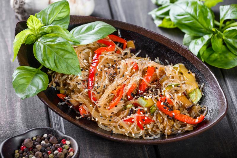 Rice noodles with vegetables and sesame seeds on wooden table. Indian cuisine stock images