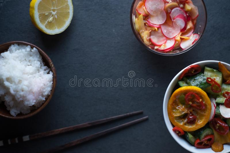 Rice, pickled vegetables, lemon and chopsticks free space. Asian cuisine. Horizontal royalty free stock image