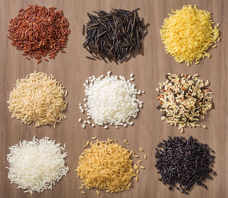 Rice. Piles of different rice varieties over a wooden background including jasmine, basmati, wild rice, risotto and parboiled in Red, white, brown and black stock photo