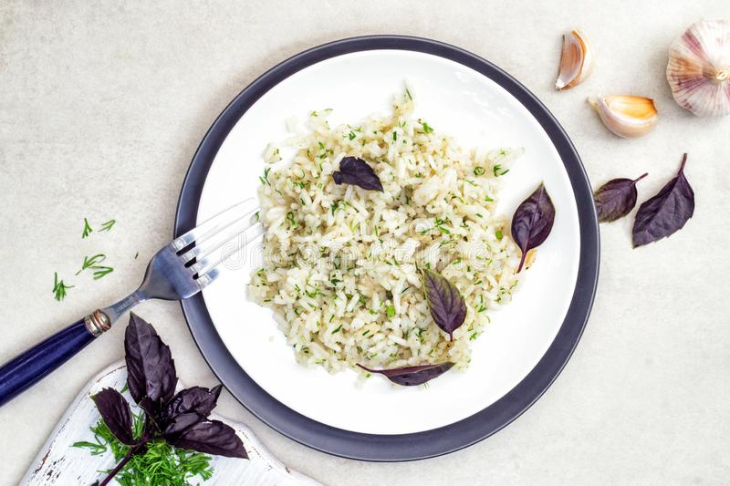 Rice in a plate with herbs, basil and garlic on a white table. Rice in a white and black plates with herbs, basil and garlic on a white table. Top view royalty free stock image