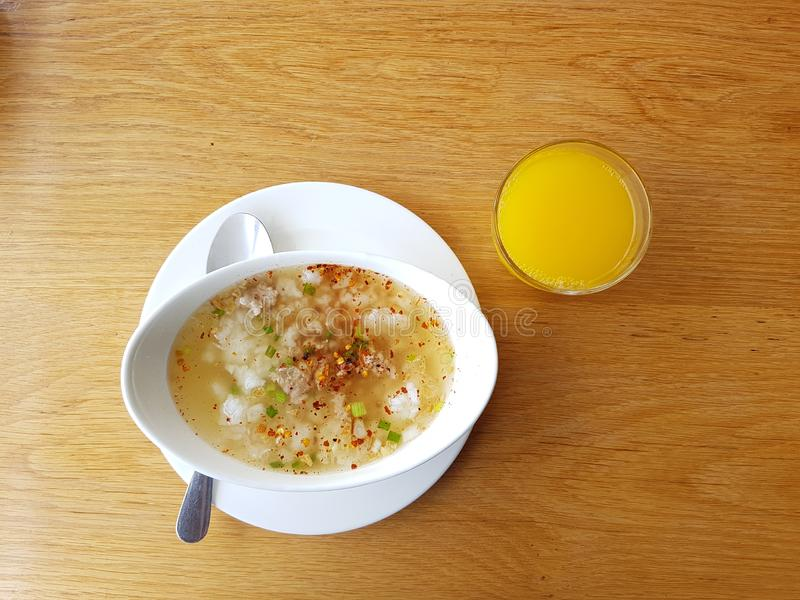 Rice with Pork boiled breakfast with the Orange Juice and Drinking Water on woodeb table. & x28;Asia traditional food royalty free stock photo