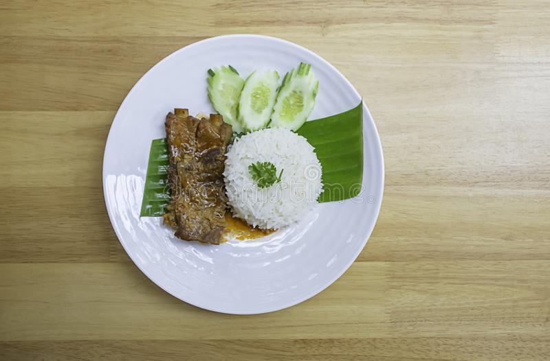 Rice and Pork Ribs On banana leaves With cucumbers on a white plate on wooden  table royalty free stock photos