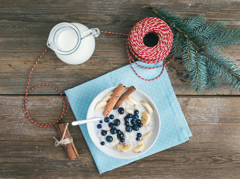 Rice porridge with milk, cinamon, banana and blueberry with Christmas (New Year) decorations on a rustic wood background royalty free stock image
