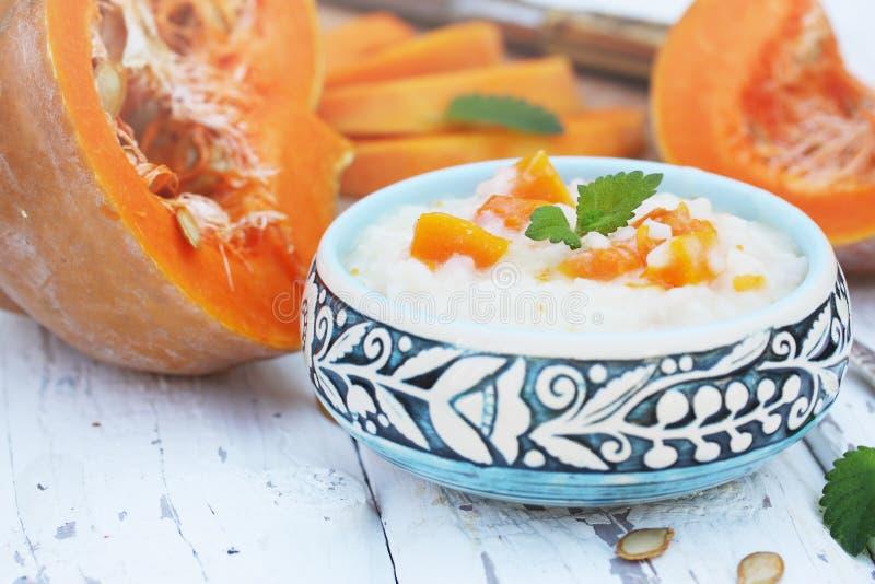 Rice porridge. Milk rice porridge with pumpkin on a wooden board stock photo