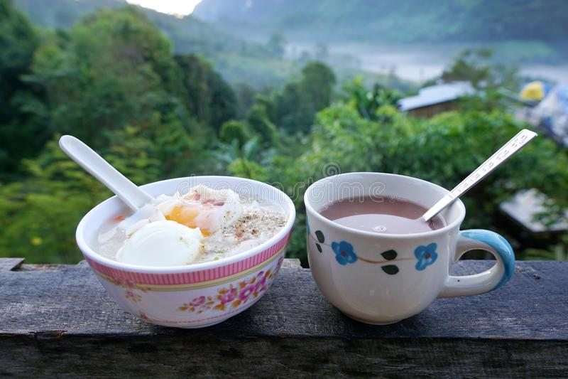 Rice porridge with parboiled egg, minced pork, pepper and Hot chocolate on wooden table. royalty free stock photography
