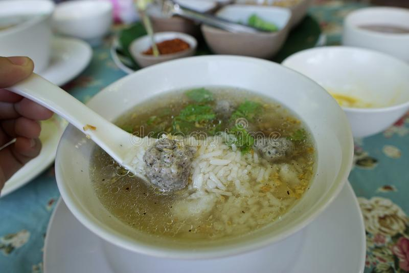Rice porridge with parboiled egg, minced pork and pepper on the table stock images