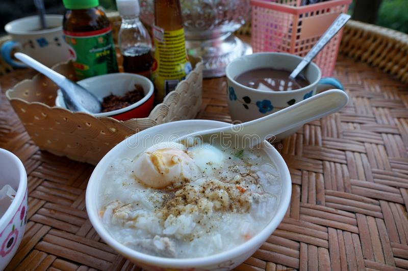 Rice porridge with parboiled egg, minced pork and pepper on wooden table, rice gruel or congee in forest. stock image