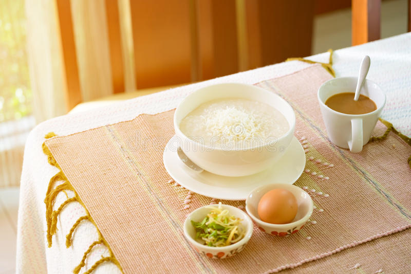 Rice porridge, rice gruel or congee with pork, egg, sliced ginger and vegetable stock photography