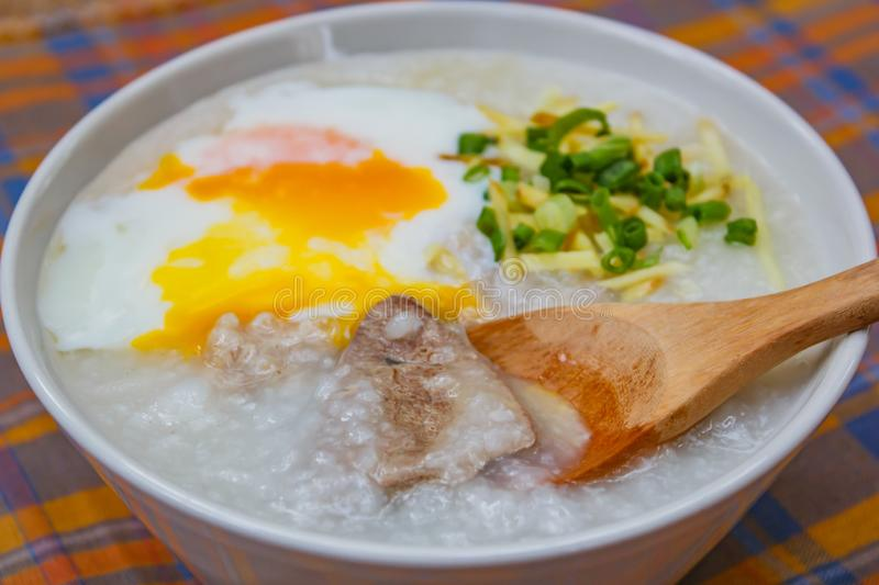 Rice porridge with soft boiled egg, ginger and chopped spring onion stock images