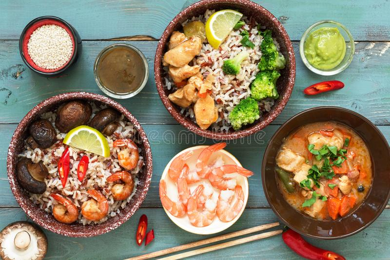 Rice with prawns, chicken, mushrooms, broccoli on a naked rustic background. Asian dishes. Concept of Asian food. View from above. stock images