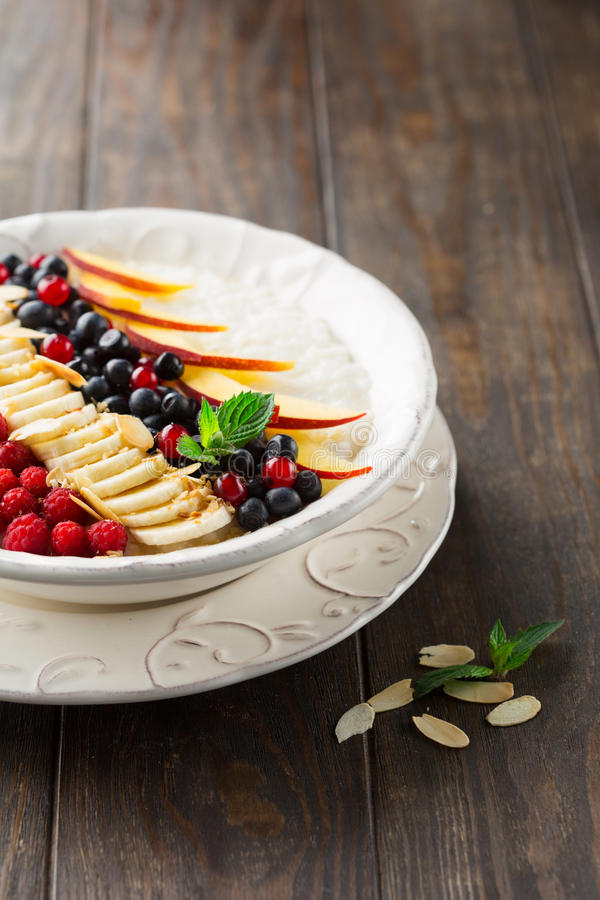 Rice pudding with fresh fruits. Breakfast rice pudding with fresh fruits, vanilla and almond in a bowl on rustic wooden backgrouns, selective focus royalty free stock image