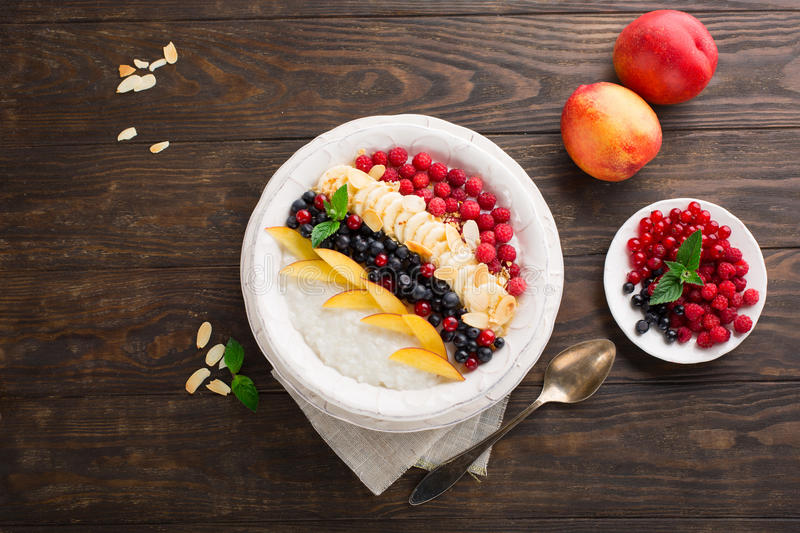 Rice pudding with fresh fruits. Breakfast rice pudding with fresh fruits, vanilla and almond in a bowl on rustic wooden backgrouns, top view royalty free stock images