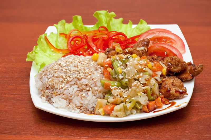 Rice with roasted meat and vegetables stock photos