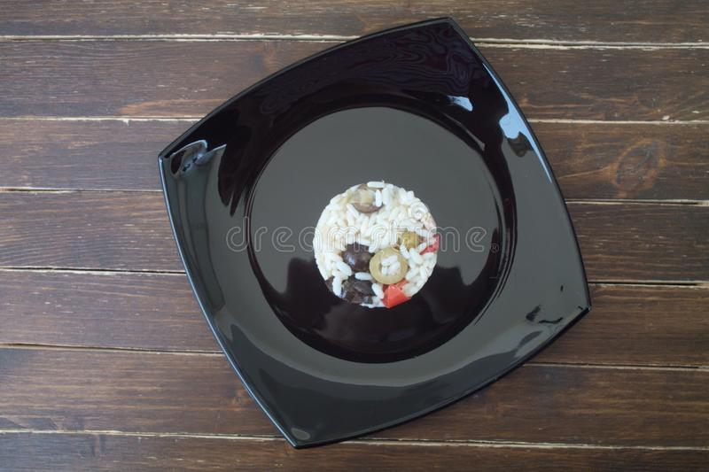 Rice salad in a black dish on wood from above royalty free stock photography