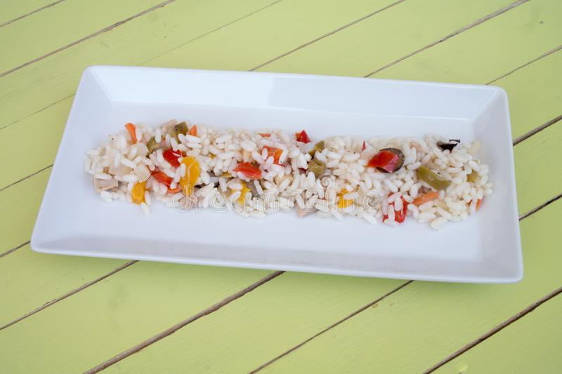 Rice salad in a white tray on green wood royalty free stock image