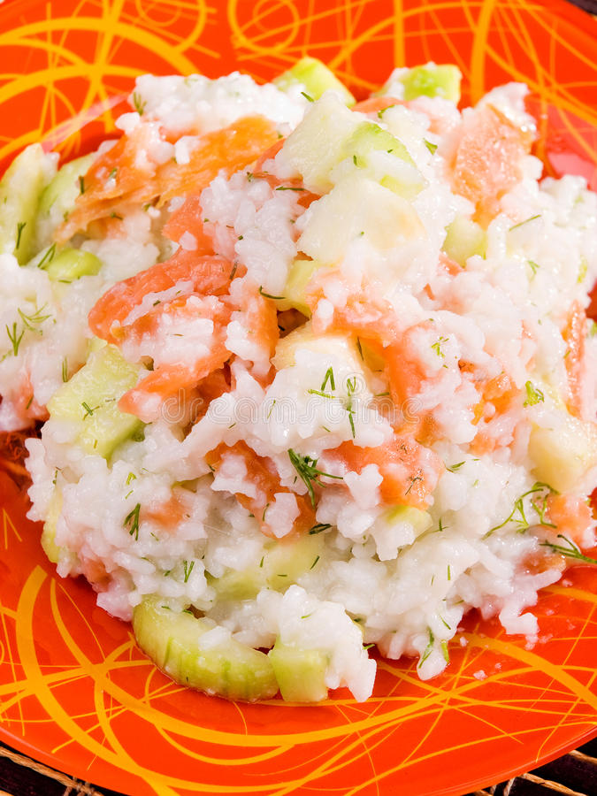 Rice with salmon and cucumbers salad. Shot from above stock images