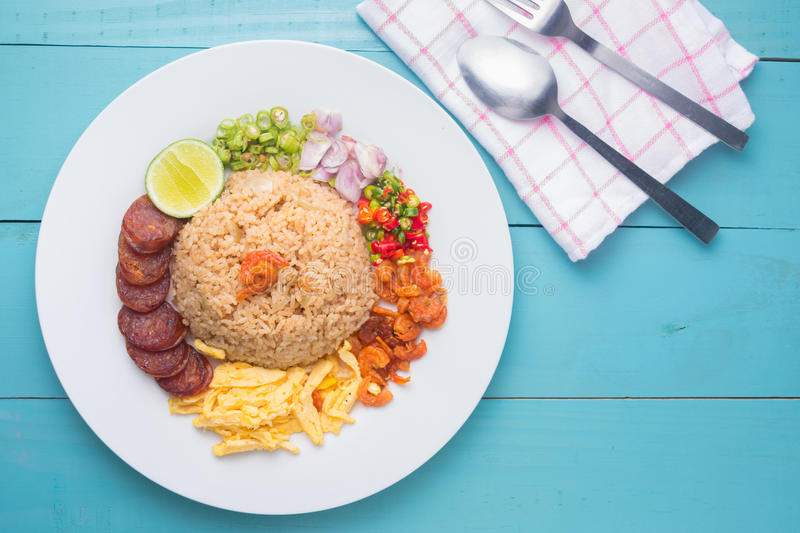 Rice Seasoned with Shrimp Paste, Thai food on white dish over wooden table. stock photo