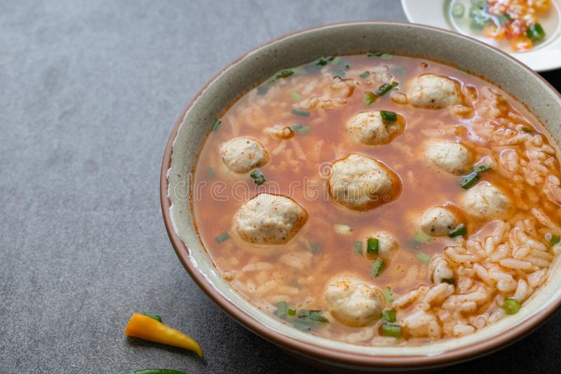 Rice spicy soup with chicken ball and chilli in gray bowl on table royalty free stock photography