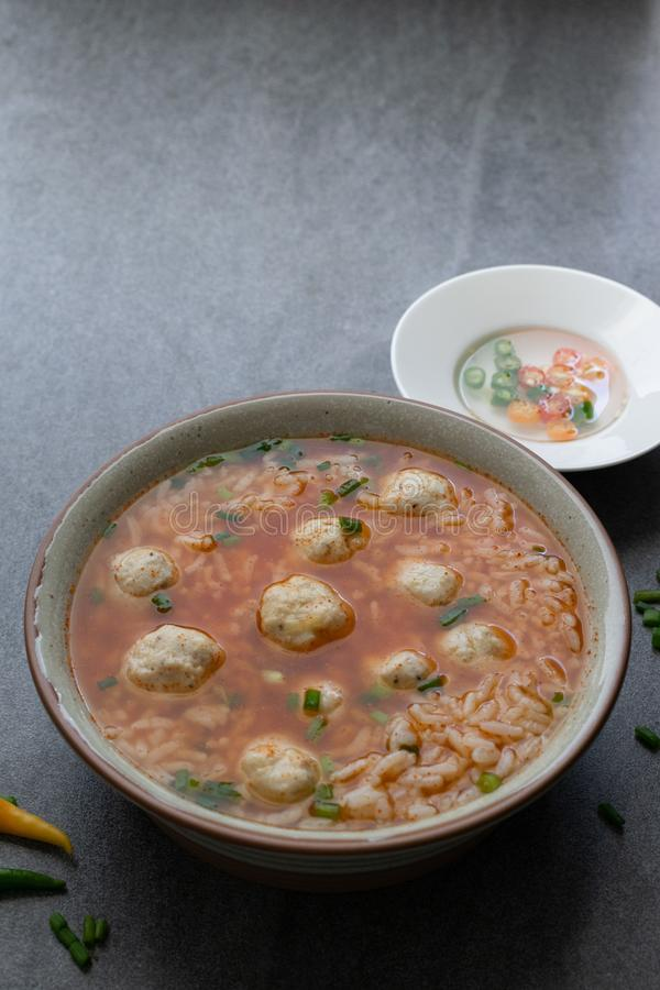 Rice spicy soup with chicken ball and chilli in gray bowl on table royalty free stock image
