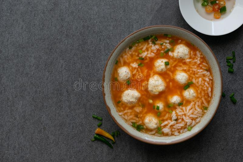 Rice spicy soup with chicken ball and chilli in gray bowl on table royalty free stock photos