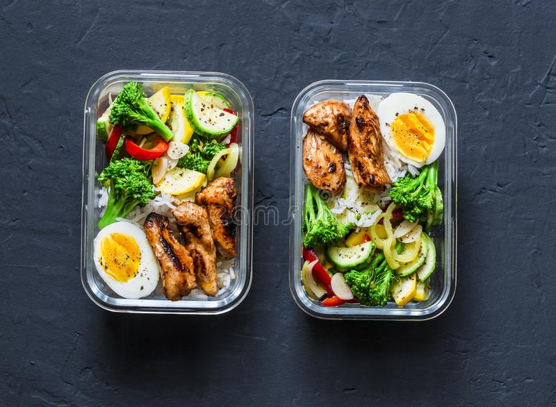 Rice, stewed vegetables, egg, teriyaki chicken - healthy balanced lunch box on a dark background, top view. Home food for office. Concept stock photo